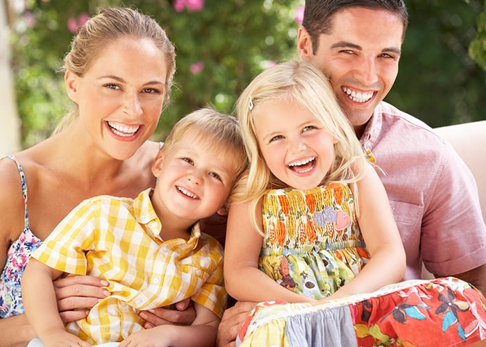 A family with perfect, healthy teeth smile for a group photo.